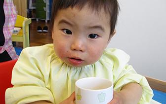 陶器食器を両手で持つ園児